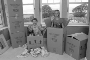 Children playing in boxes while packing for house move